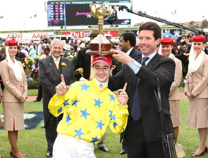 Christophe Lemaire (yellow) and trainer Mikel Delzangles celebrate after winning the Emirates Melbourne Cup with Dunaden.