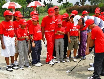 Charl Schwartzel advising young golfers on how to use the sand wedge at the Emirates golf clinic